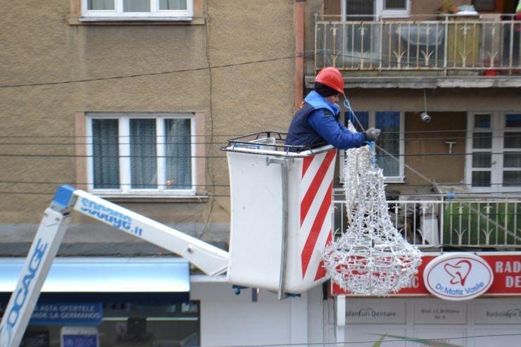 Se montează noile ghirlande și ornamente stradale pentru sărbătorile de iarnă